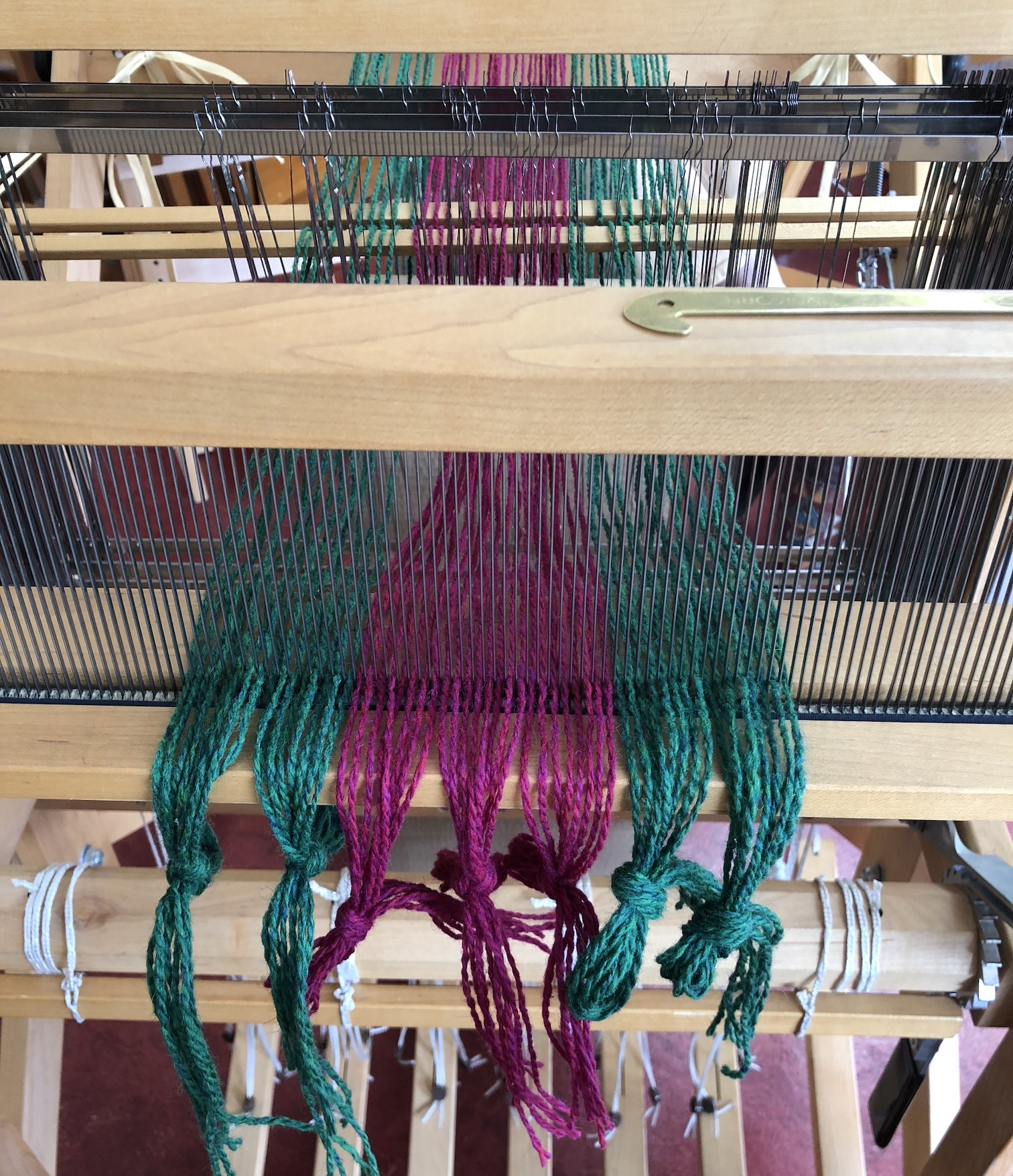 Warp threads going through the reed, before weaving had begun. On top of the reed rests the metal hook I used to pull them through